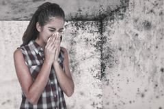 Composite image of sick blonde woman sneezing in a tissue Stock Photos
