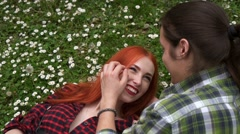 A young man puts a flower into the hair of a girl Stock Footage
