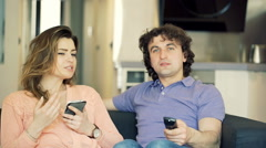 Couple relaxing on the sofa at their apartment, steadycam shot Stock Footage