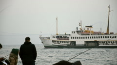 One of Passenger ferryboat of Istanbul is landing, people fishing Stock Footage