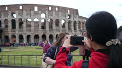 Tourists make smart phone photo of Colosseum in Rome Italy Stock Footage