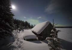 Village house in the lights of moon and Aurora borealis. Northern Karelia. Russi Kuvituskuvat