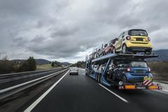 Auto transporter laden by multicolored small cars is on the road - stock photo