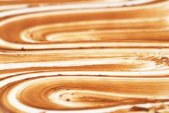 Melted chocolate spread over white background Stock Photos