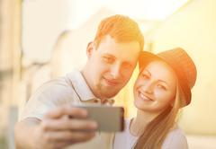 Touristic couple shooting on the modile phone selfy at the city - stock photo