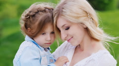 Portrait of mum with a daughter 4 years, leaning against each other Stock Footage