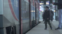 Little boy making farewells at railway station, waving hand to friend on a train Stock Footage