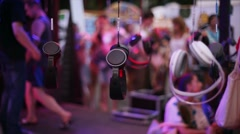 Many headphones hang on wire at open air festival party. Entertainment. Holidays Stock Footage