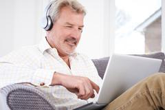 Mature Man Streams Music From Laptop To Wireless Headphones Stock Photos