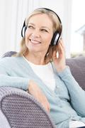 Mature Woman Listening To Music On Wireless Headphones - stock photo