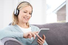 Mature Woman Streams Music From Digital Tablet To Wireless Headphones - stock photo