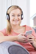 Woman Streams Music From Mobile Phone To Wireless Headphones - stock photo
