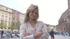 Girl putting her sunglasses on forehead. Old town background. Slow motion - stock footage