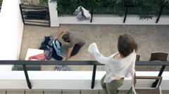 Couple fighting, woman throwing out clothes from terrace, super slow motion  Stock Footage