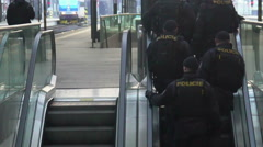 Police officers on moving escalator. Patrol providing safety at railway station Stock Footage