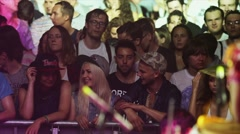 Crowd of people dance on night open air party. Spotlight. Boy start speak with - stock footage