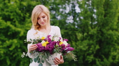 Beautiful blonde woman with a bouquet of lilacs. It stands on a background of Stock Footage