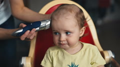 Mother doing a haircut for a baby boy with a hair clipper Stock Footage