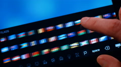 The man is looking at the correspondence flags of the countries on a Tablet PC. - stock footage