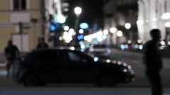 Out of focus shot of a city scene at night with fancy lights and walking - stock footage