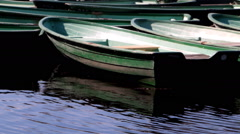 Boat landing, dock. Moored green boats dancing on the wavelets Stock Footage