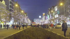 Happy people walking in beautiful decorated city center, evening time, tourism Stock Footage