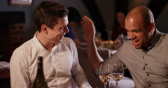 4K Smart-casual men chatting & laughing over a glass of wine in restaurant Stock Footage