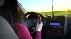 Woman driver driving a car toward sunset, pov Stock Footage