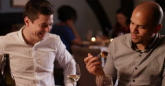 4K 2 Young men laughing & enjoying a meal out, man offers his companion a taster Stock Footage