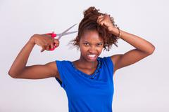 Young African American woman cutting her frizzy afro hair with scissors - Bla Stock Photos