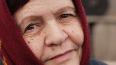 an elderly woman in a scarf smiles sadly outdoors - stock footage