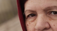 sad eyes of an elderly woman in a headscarf - stock footage