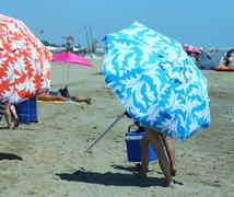 holiday makers move on the hot sand with beach umbrellas - stock photo
