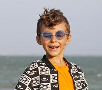 Cute little boy at seacoast in fashion clothers and blue glasses Stock Photos
