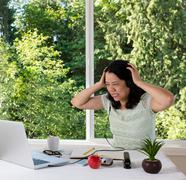 Mature woman in anger will working from home - stock photo