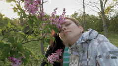 Two girls sniffing lilac flowers in the green park Stock Footage