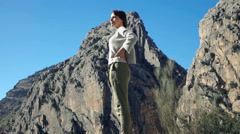 Young, pretty woman enjoying sunny day and mountain view in country Stock Footage