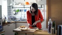Woman cutting tomato and preparing sandwich in kitchen at home Stock Footage