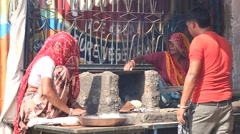 Two Rajasthani women and man preparing chapatis on fire, Pushkar. India Stock Footage