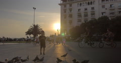 People walking around the square with pigeons at sunset Stock Footage