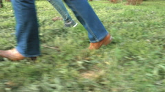 Women's feet on the grass in shoes and sneakers Stock Footage