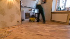 Carpenter worker cleaning room after installing wood parquet board during Stock Footage