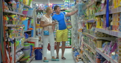 Family couple shopping for household goods in supermarket Stock Footage