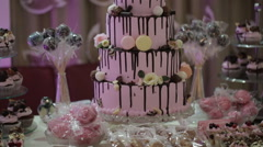 Multi-tiered wedding cake with cupcakes and macaroon Stock Footage