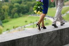 Young man and woman walking on a parapet wall - stock photo
