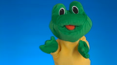Funny soft puppet frog on blue background Stock Footage