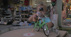 Child playing with toy bike rider in the street Stock Footage