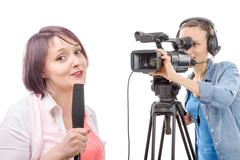 Young woman journalist with a microphone and camerawoman Stock Photos