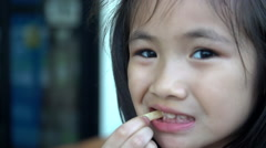 Little asian girl eating french fries and looking camera. - stock footage