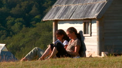 Girls reading a book next to the huts in the ethno village Stock Footage